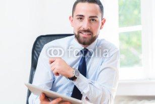Geschaeftsmann_im_Buero_mit_Tablet_Computer.jpg