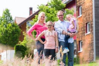 Familie-steht-vor-Haus-oder-Eigenheim-auf-Dorf-Mutter-Vater-und-zwei-Kinder.jpg