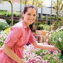 Florist_arranging_flower_pots_in_garden_store.jpg