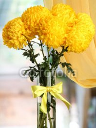 bright_yellow_chrysanthemums_in_glass_vase_on_wooden_table.jpg