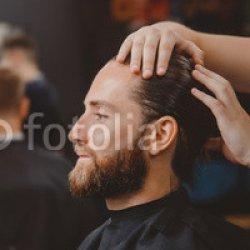 Barber-shop.-Man-in-barbershop-chair-hairdresser-styling-his-hair.jpg