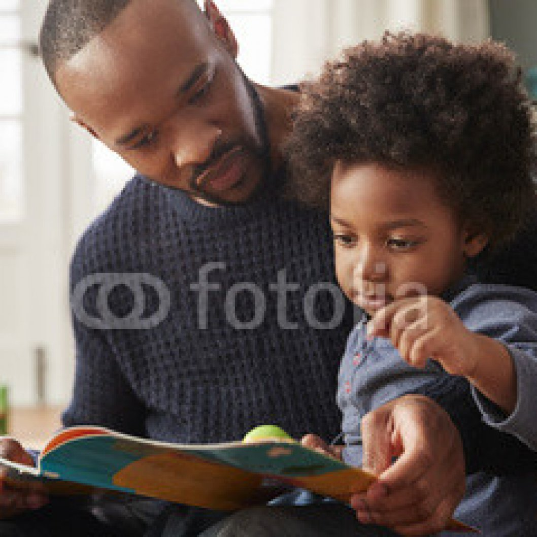 Father-And-Young-Son-Reading-Book-Together-At-Home.jpg