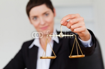 Serious_businesswoman_holding_the_justice_scale.jpg