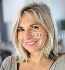 Senior_woman_standing_against_white_wall.jpg