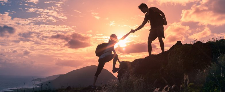 Team-work-life-goals-and-self-improvement-concept.-Man-helping-his-female-climbing-partner-up-a-steep-edge-of-a-mountain.-.jpg