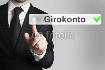Geschaeftsmann_in_Anzug_drueckt_touchscreen_Knopf_Girokonto.jpg