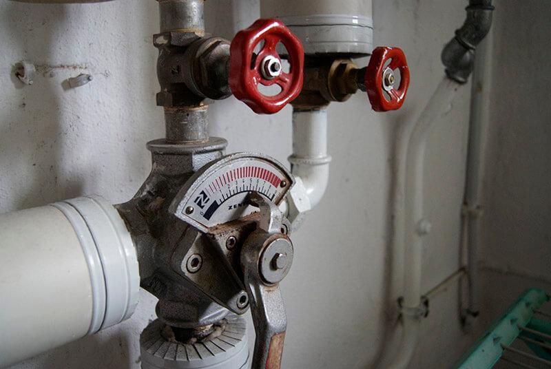 Rohre mit roten Ventilraedern im Keller in Dortmund