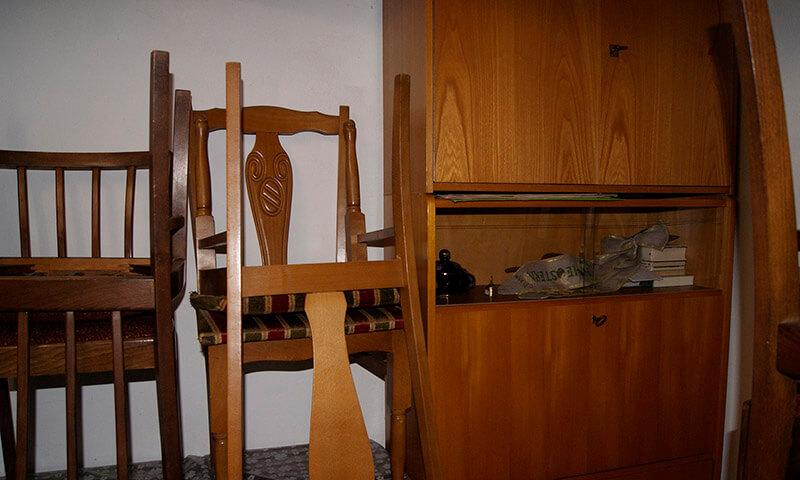 Ein alter Stuhl neben einem Schrank