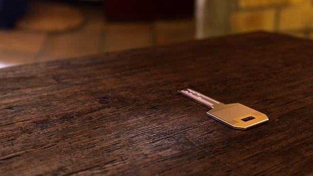 einzelner Schlüssel liegt auf Holztisch