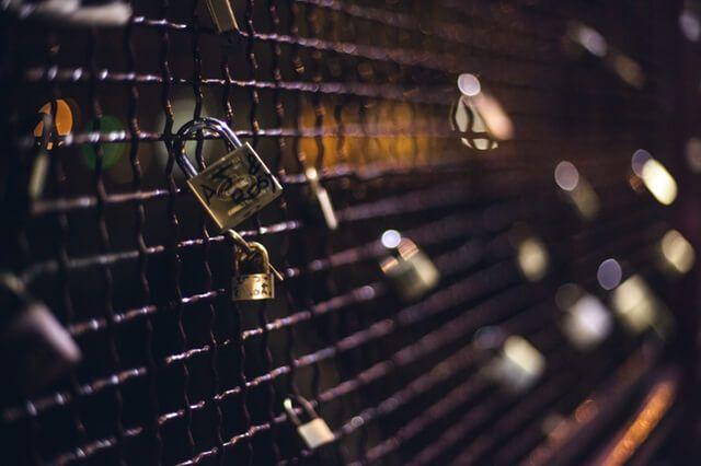 Gitter an dem viele Schlösser angebracht sind