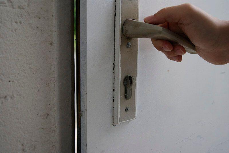 Hand öffnet weiße Türe