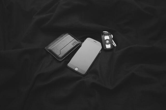 Schlüssel, Handy Geldbeutel auf schwarzem unebenen Hintergrund