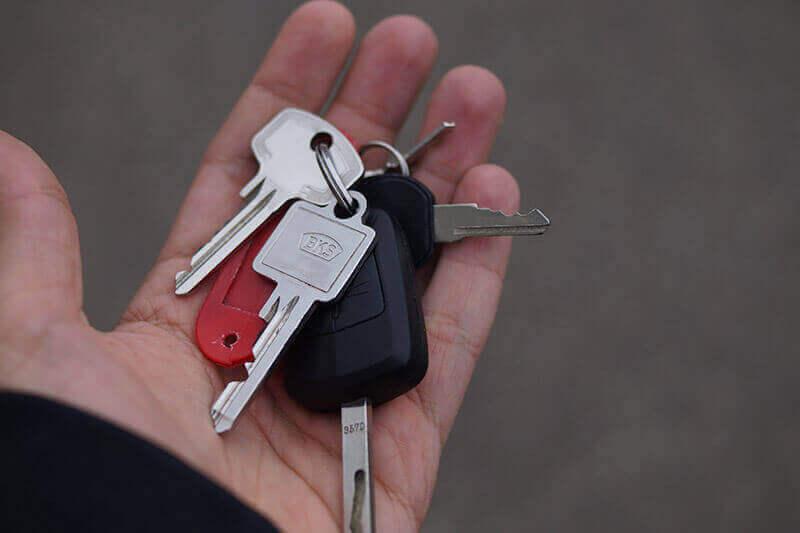 Schlüssel mit einem roten Anhänger in der Hand halten