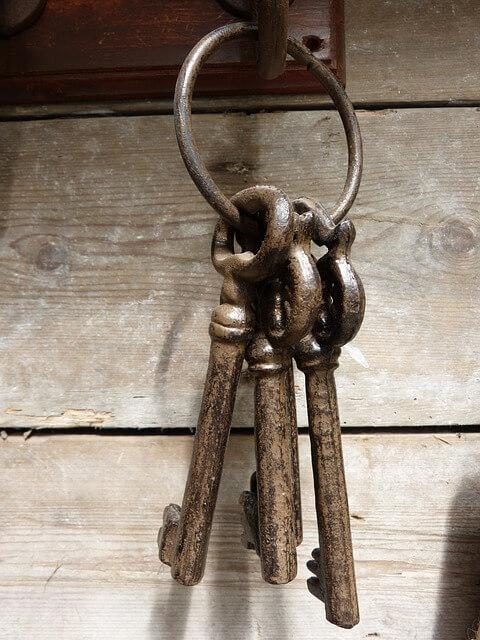 Schlüssel hängt noch an einem Hacken vor einer Holzwand