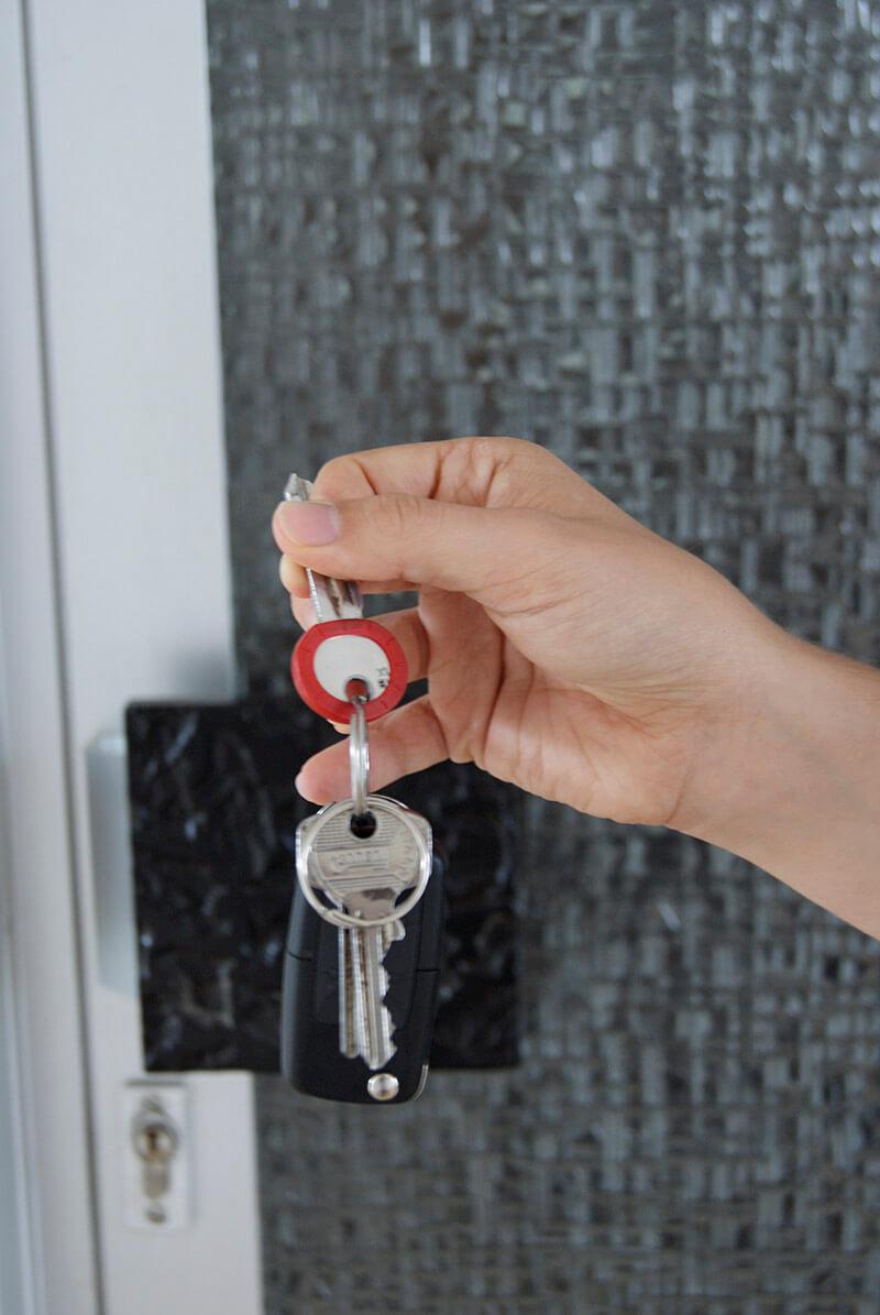 Frau hat einen Schlüssel in der Hand und steht vor der Tür