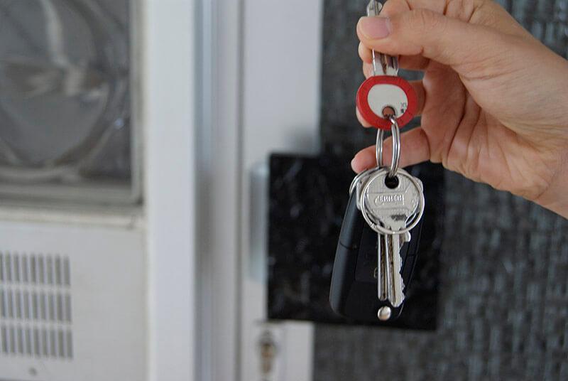 Frau hält einen Schlüssel mit roter Umrandung in Ihrer Hand
