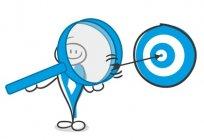 Blick durch eine Lupe auf eine Zielscheibe mit einem Pfeil im Zentrum