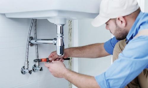 Installateur montiert Wasserhahn im Badezimmer