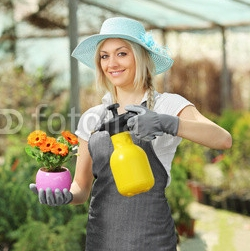A_beautiful_female_gardener_watering_a_plant.jpg
