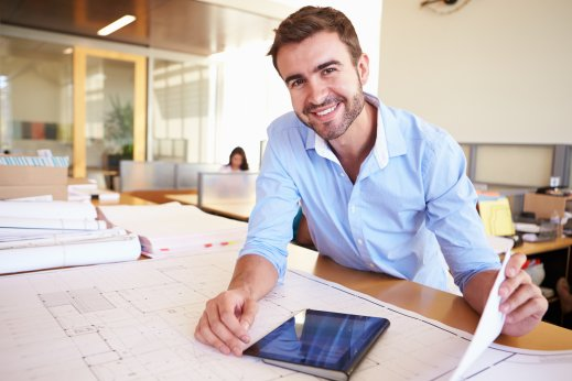 Male-Architect-With-Digital-Tablet-Studying-Plans-In-Office.jpg