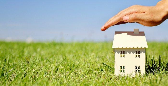 Modellhaus-auf-Rasen-mit-schützender-Hand