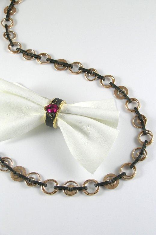 Ring aus Gelbgold und Carbon mit einem Rubelith. Collier aus Roségold und Carbon