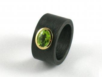 Ring aus Carbon mit einem Peridot gefasst in Gelbgold