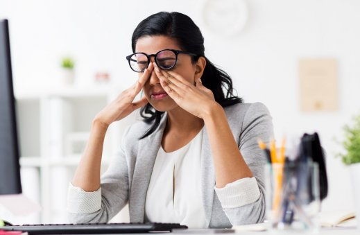 businesswoman-rubbing-tired-eyes-at-office-P3KFDGD.jpg