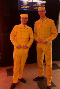 Walkact in gelber Hotelpagen Uniform